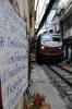 "DSVN D19E-948 heads south from Hanoi, through ""Railway Street"" with SE35 1310 Hanoi - Vinh"