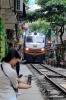 "DSVN D19E-942 heads south from Hanoi, through ""Railway Street"" with SE9 1430 Hanoi - Saigon"
